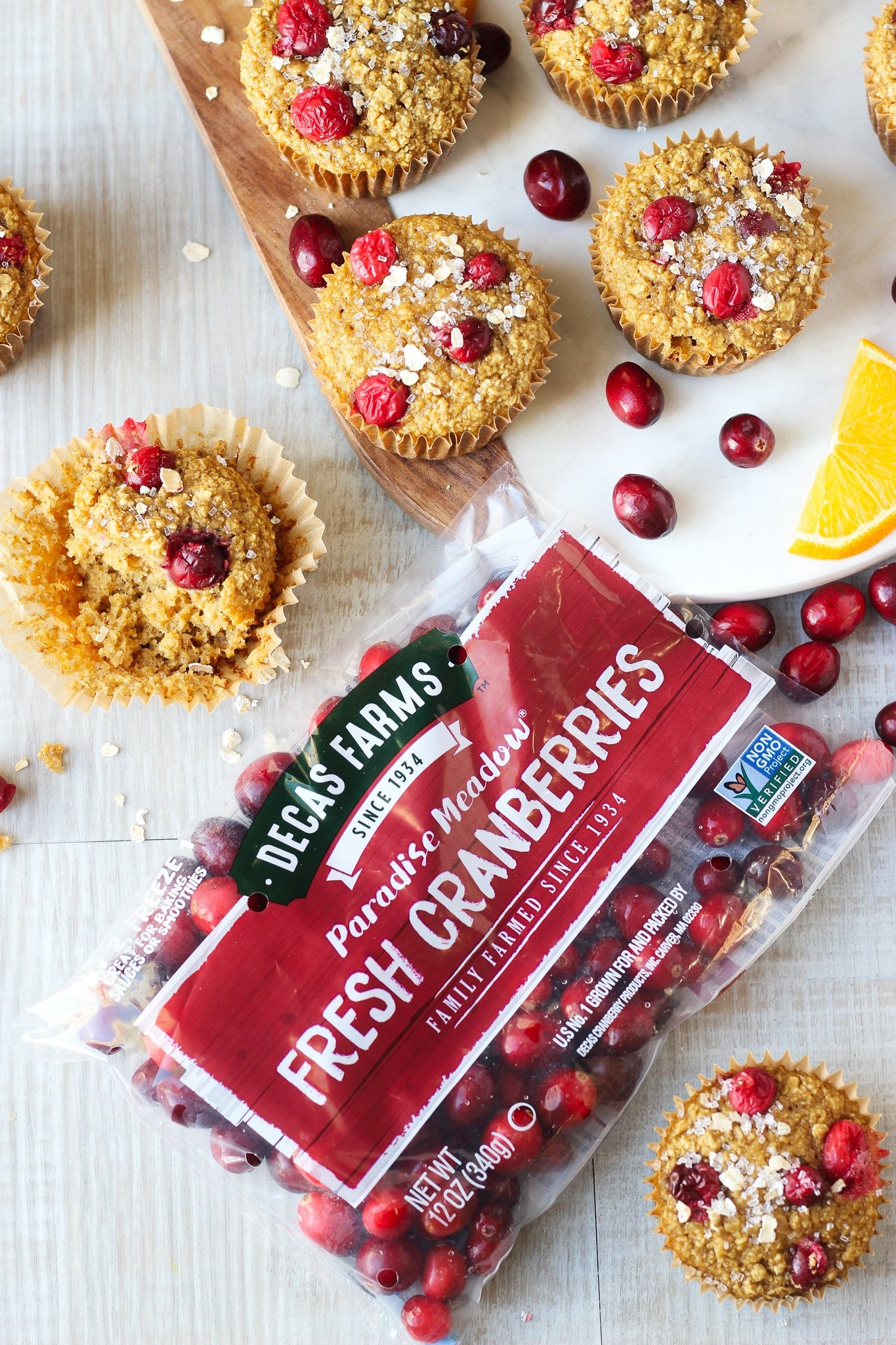 A pack of fresh Cranberries beside some muffins, fresh cranberries and orange slices