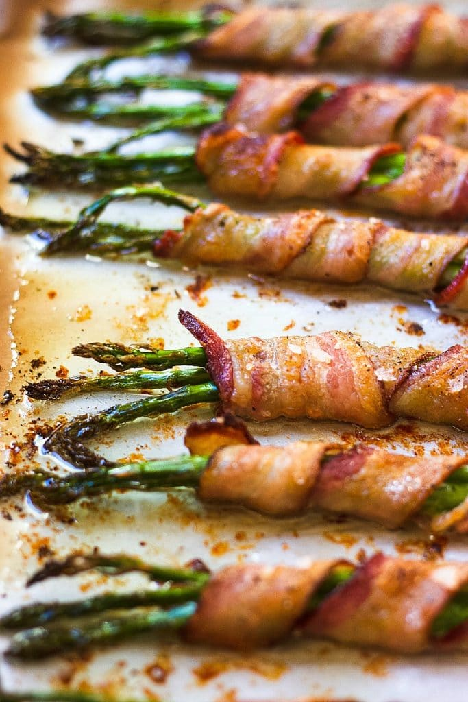 Cooked bacon wrapped asparagus in a baking sheet lined with parchment paper