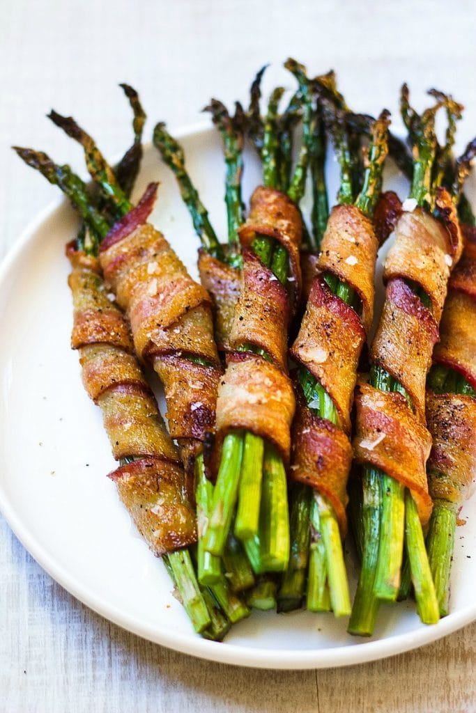 Asparagus and bacon topped with sea salt in a round white plate