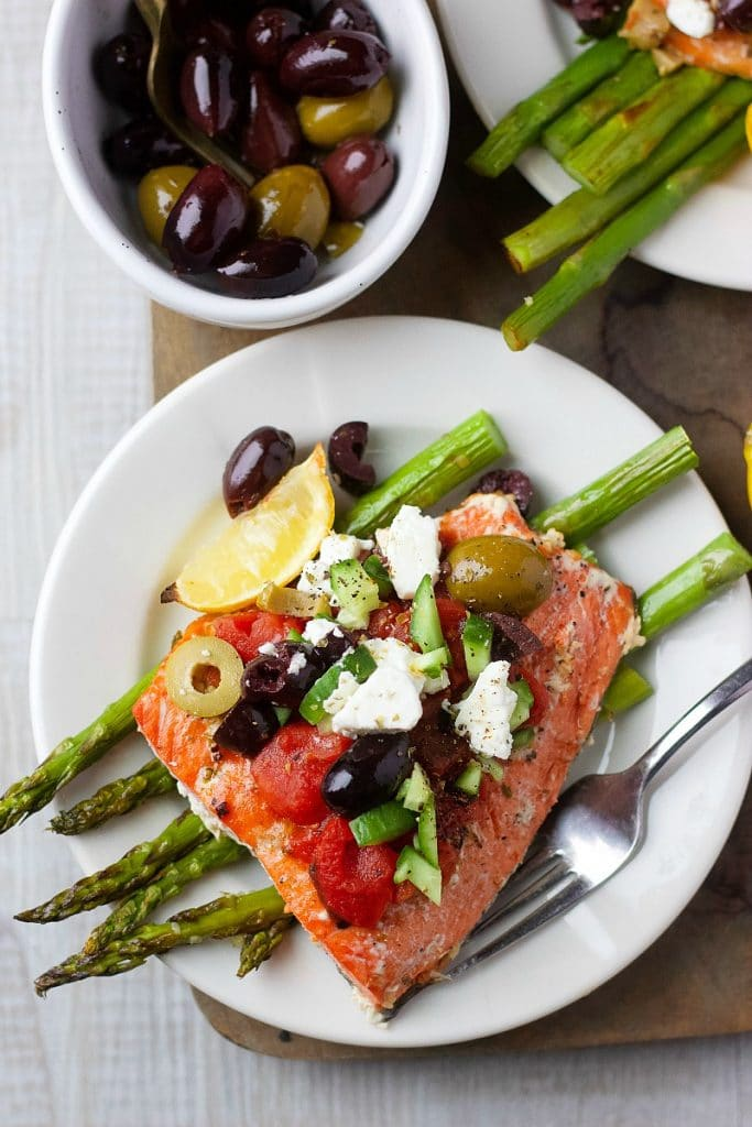 Baked salmon with Mediterranean Salad on a small white plate with fork
