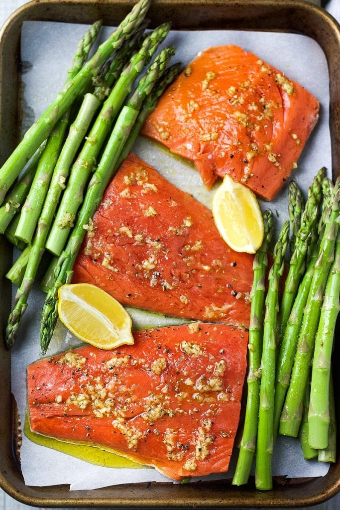 Fresh salmon with asparagus and slices of lemon on a sheet pan