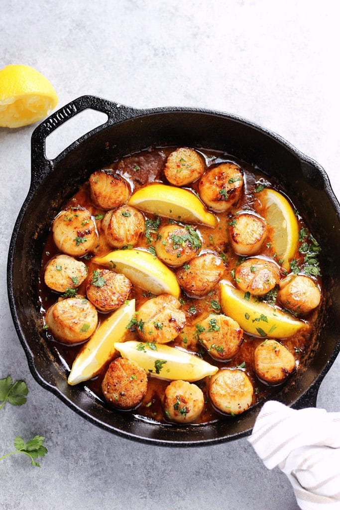 Cast iron skillet containing pan seared scallops in butter and lemon