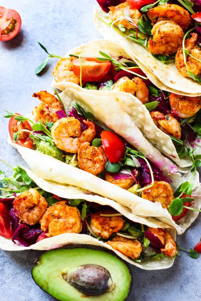 Shrimp, greens, tomatoes in each grain-free tortilla with half of an avocado
