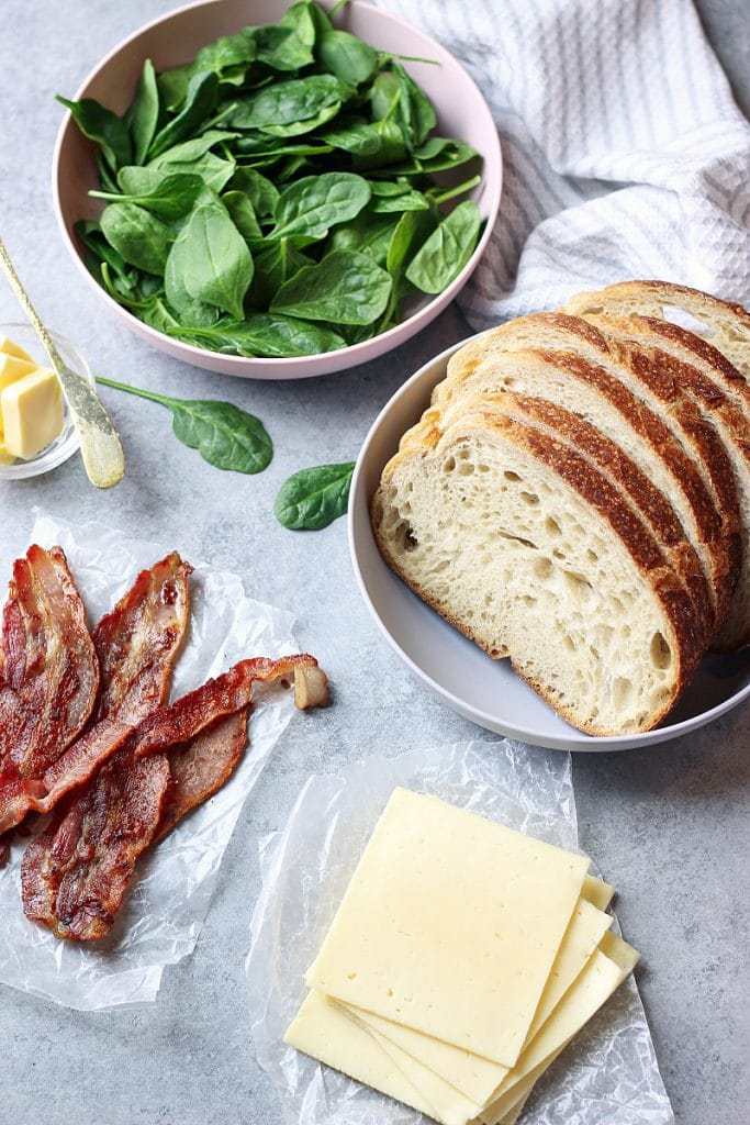 Bowls of spinach and bread slices as well as cheese and bacon