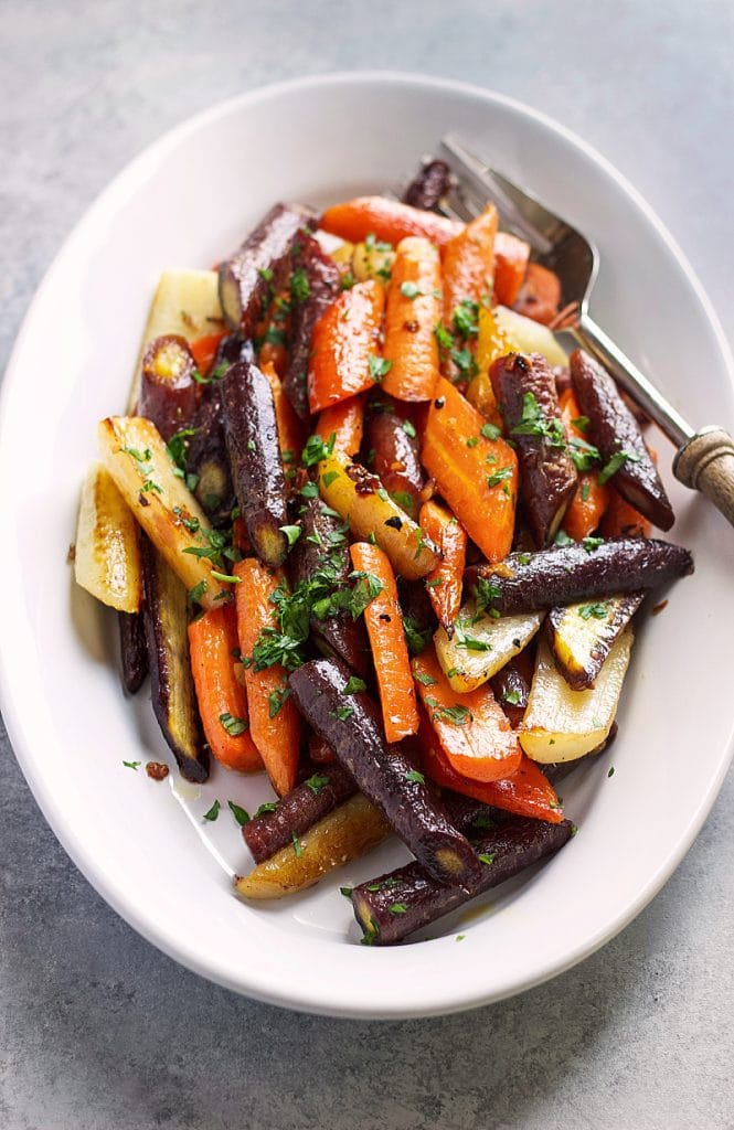 Roasted carrots served in an oval white plate with a serving fork.