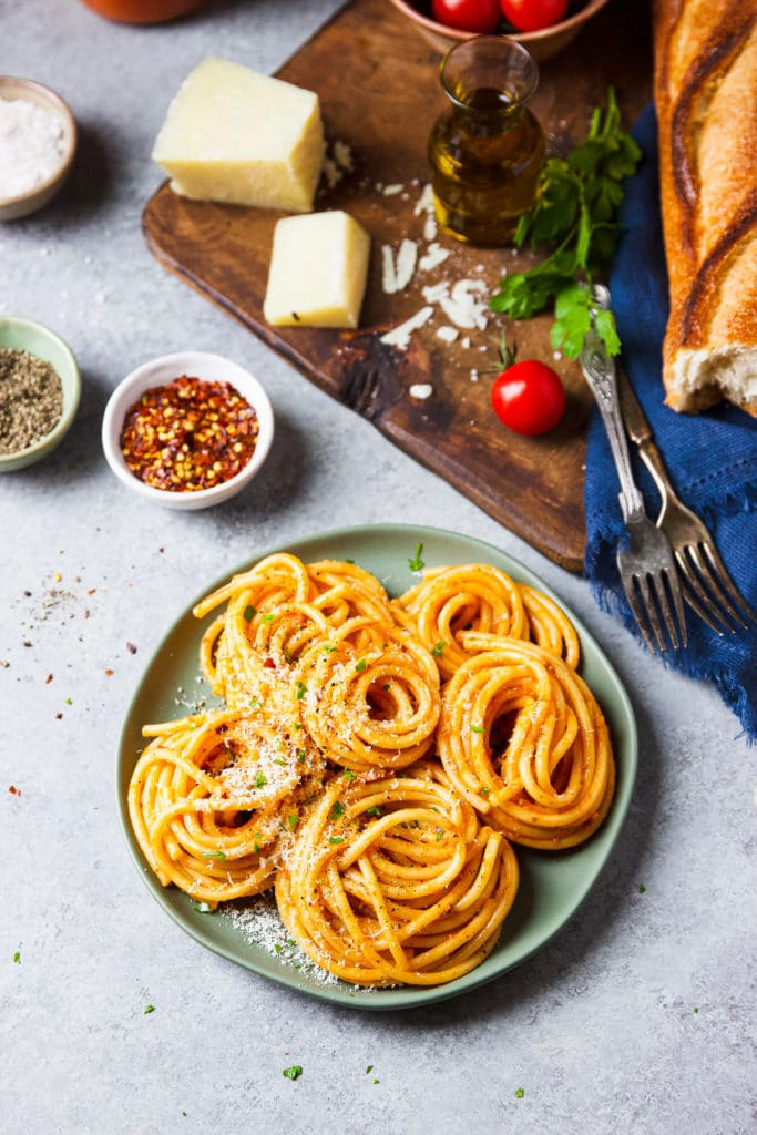 Tomato-based pasta on a plate surrounded by small bowls of red pepper flakes and black pepper, a chopping board with French bread, a cherry tomato, a slice of cheese and two forks