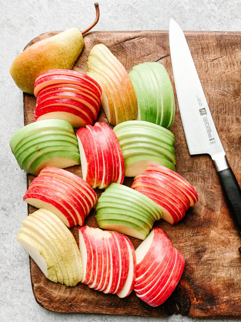 Evenly sliced apples and pears on a chopping board with knife