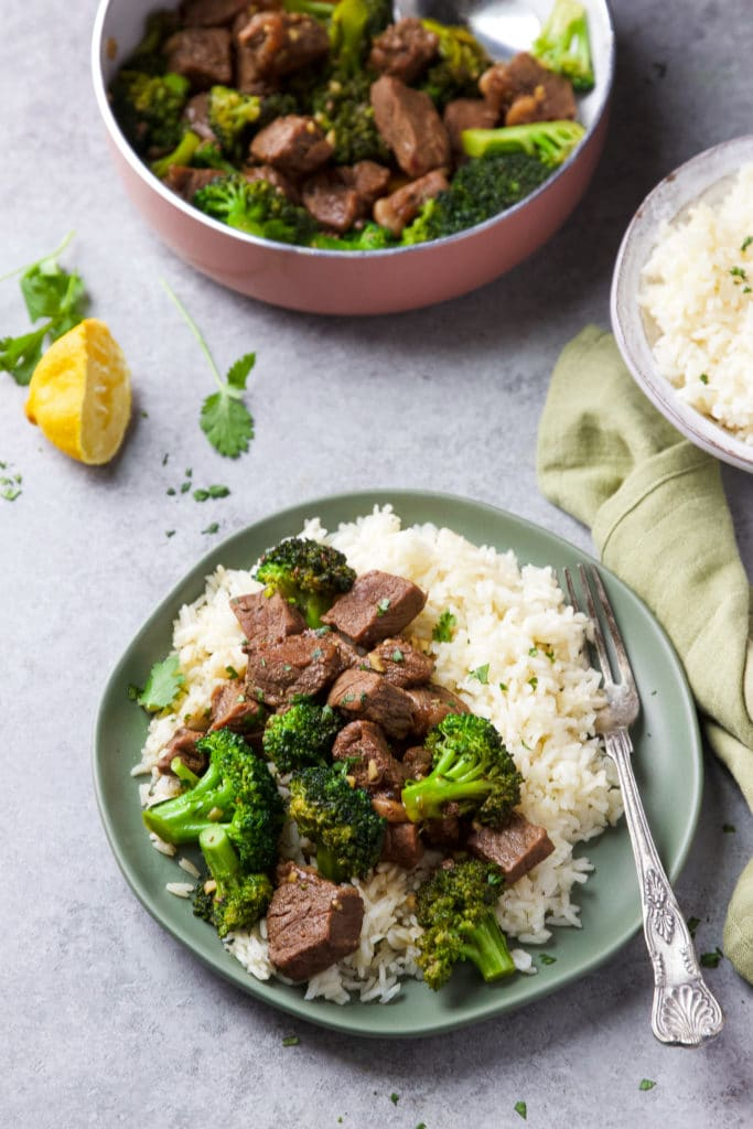 A Chinese dish of beef and broccoli with white rice on a plate