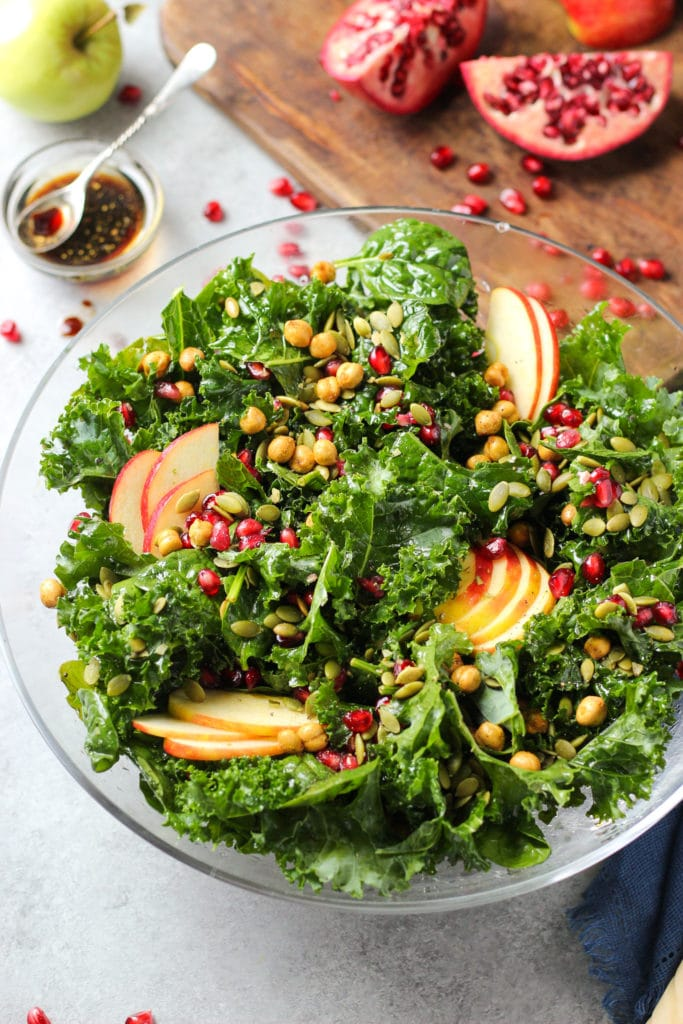 Salad greens topped with colorful seeds in a large glass bowl surrounded by a small bowl of dressing and pomegranate slices on a chopping board