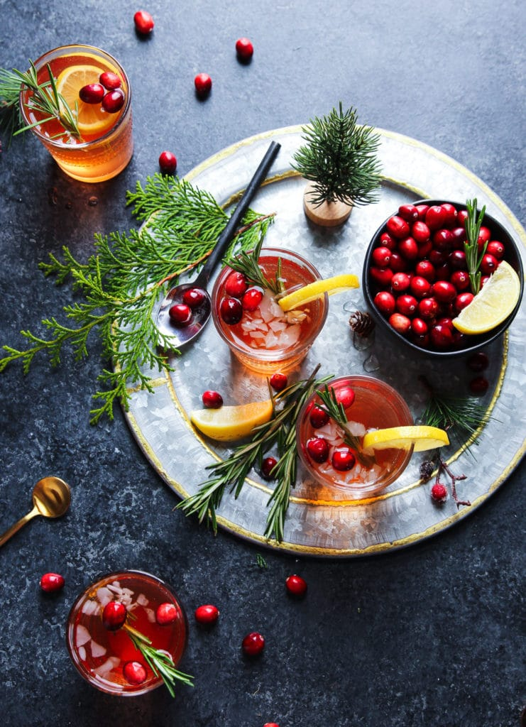 Glass of an cranberry spritzer with wine topped with lemon, rosemary sprigs and fresh cranberries