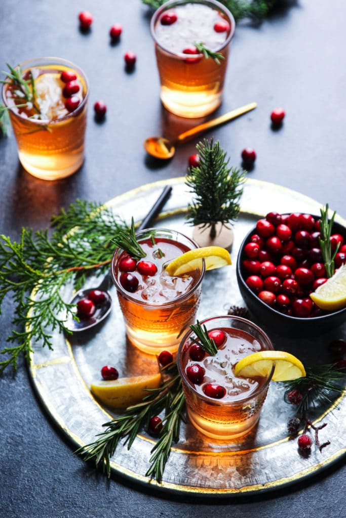 Glass of an alcoholic beverage topped with lemon, rosemary sprigs and fresh cranberries