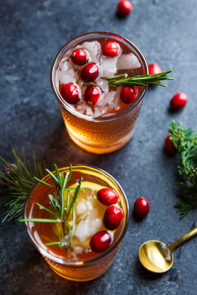 Two glasses of an alcoholic beverage  with ice cubes and topped with lemon, fresh cranberries and rosemary twigs.