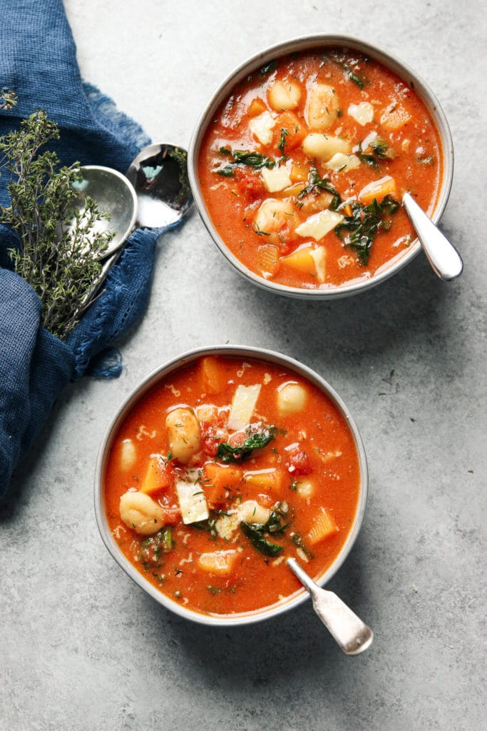 Tomato Gnocchi Soup in two bowls with a spoon