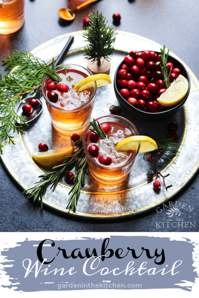 Cranberry Wine Spritzer in two glasses on a charger plate with a bowl of fresh cranberries
