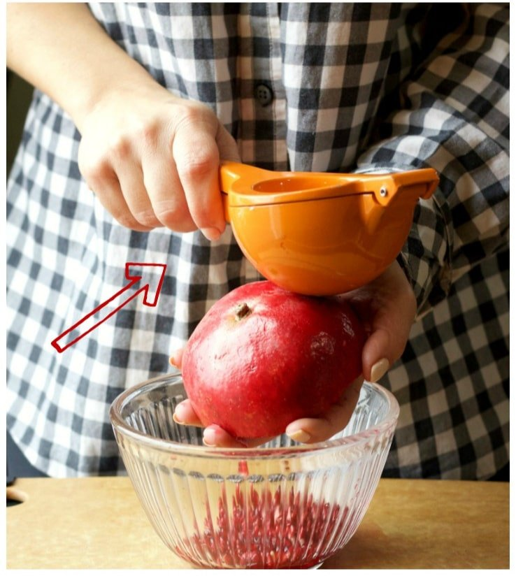 A heavy citrus squeezer on a half slice of pomegranate held by a hand on top of a glass bowl