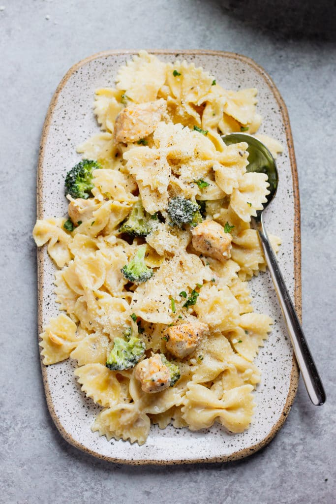 creamy Alfredo sauce pasta with chicken and broccoli, on a plate with a spoon.