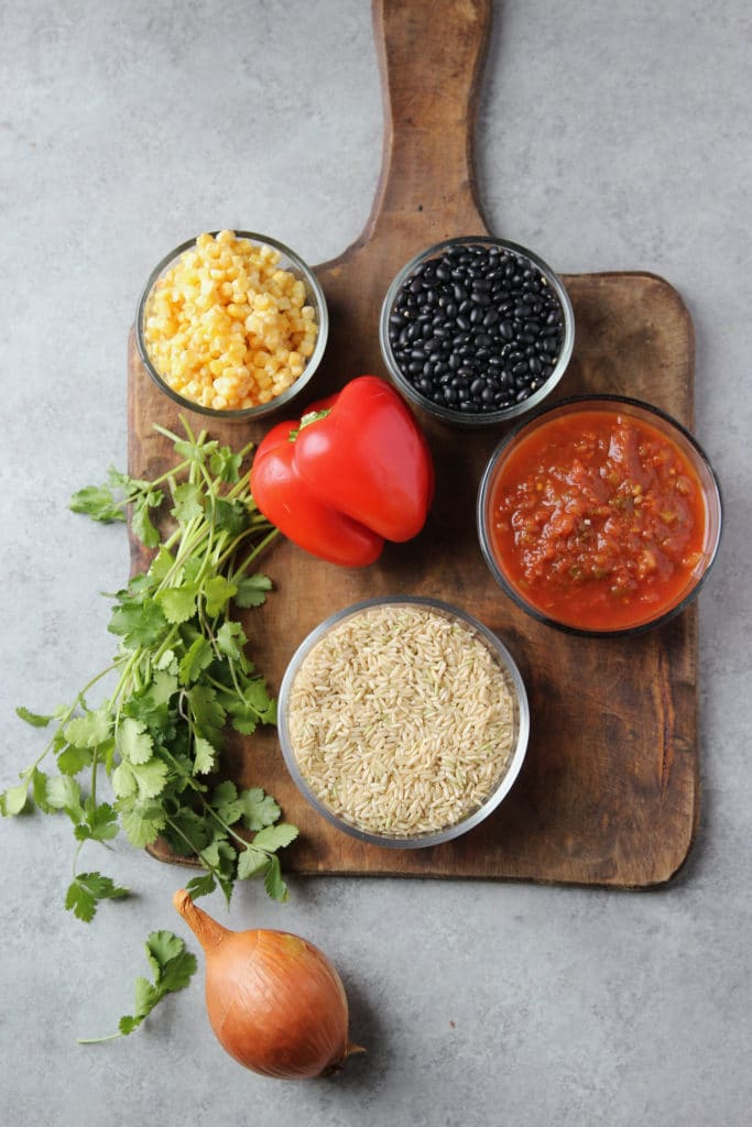 Small glass bowls each containing corn, black beans, chunky salsa, rice. With it are whole bell pepper, white onion and cilantro on a wooden chopping board.