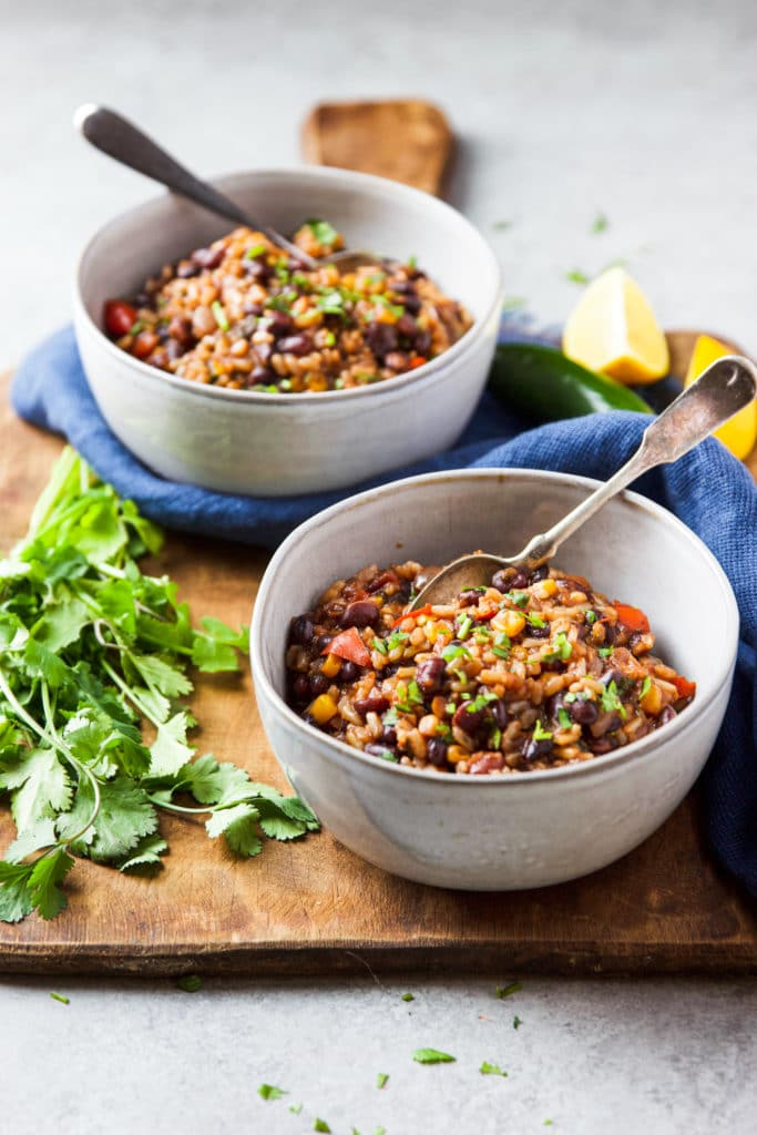 Two white bowls with a spoon containing Mexican beans and rice surrounded by lemon wedges and cilantro on a wooden chopping board
