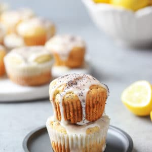 Gluten-Free Lemon Poppy Seed Muffins on top of another topped with icing and some muffins and whole lemons in the background