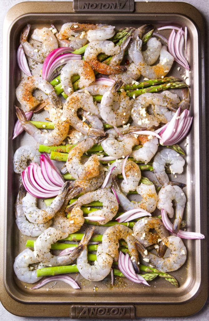 Raw shrimp, onions, and asparagus mixed with seasonings and feta cheese in a sheet pan