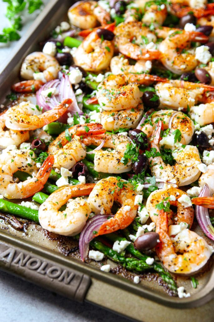 Baked shrimp with its nice orange color mixed with onions, asparagus, and black olives topped with feta cheese and parsley in a sheet pan
