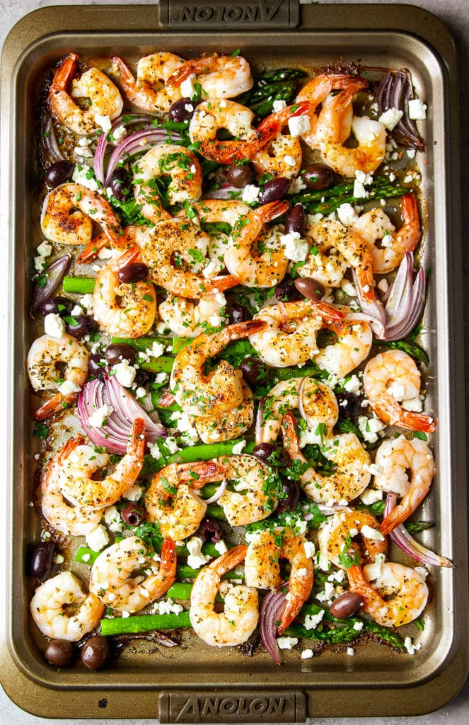 Shrimp, onions, and asparagus mixed with seasonings and feta cheese cooked in a sheet pan