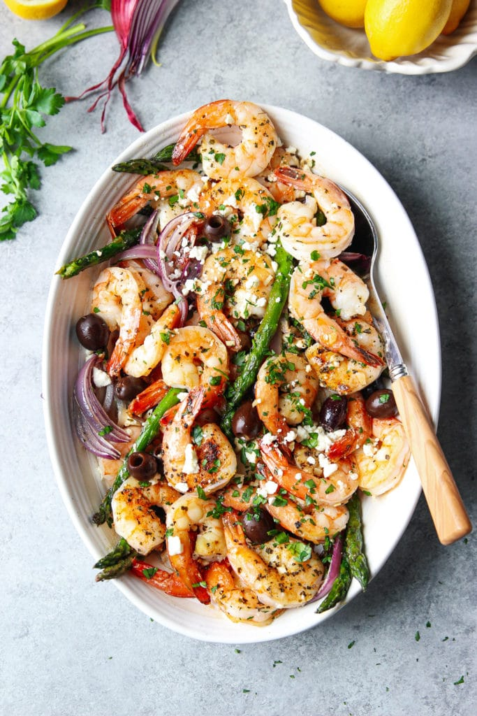 Baked shrimp with vegetables in a white oval plate with a spoon