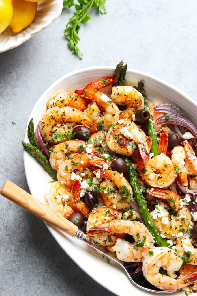 Mediterranean shrimp recipe with asparagus, onions, black olives, and feta cheese served in a white oval plate with a spoon