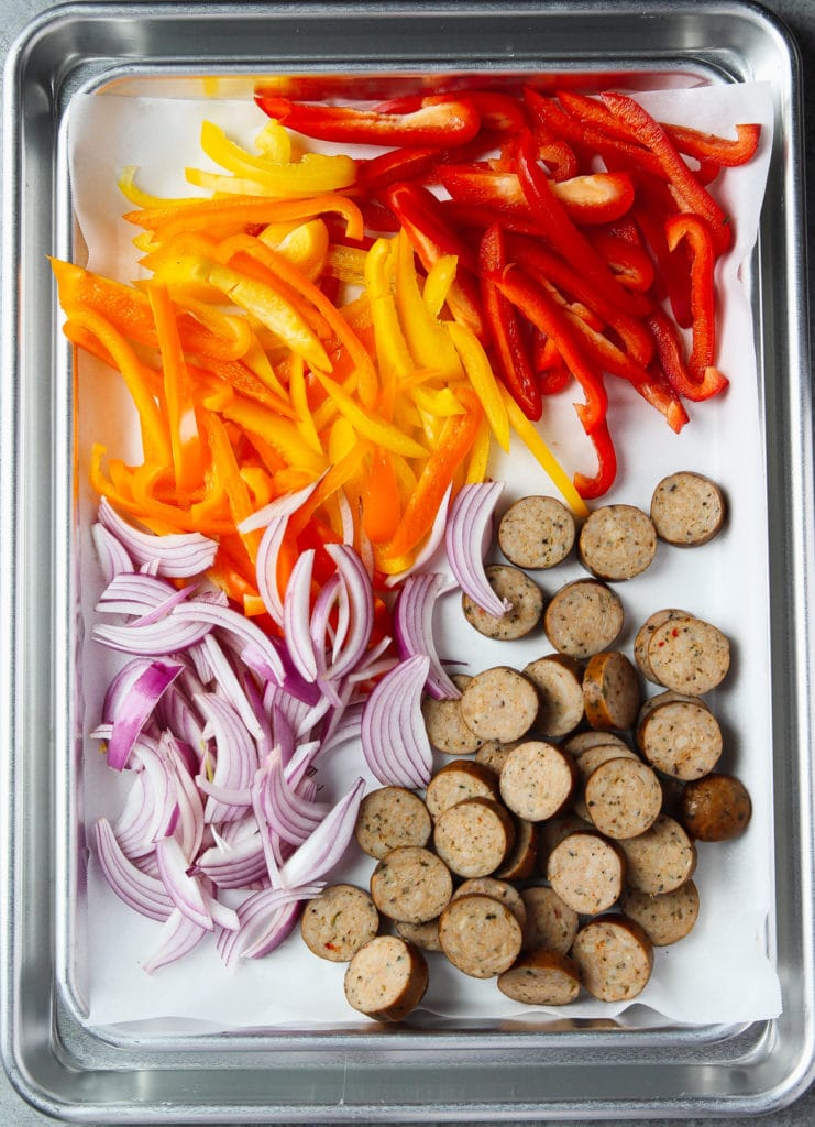 Bell peppers, onion and chicken sausages sliced arranged in a sheet pan lined with parchment paper