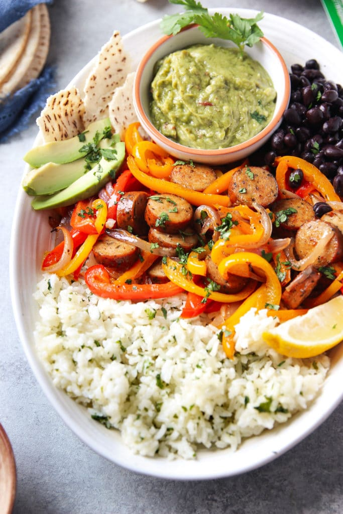 Sheet pan chicken sausage fajitas served in an oval-shaped bowl with rice, beans, slices of avocado, flat bread and a small bowl of guacamole