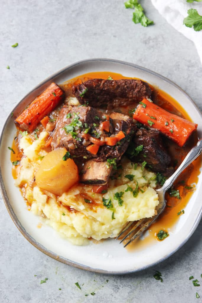 beef stew with short ribs, potatoes and carrots served over mashed potatoes on a round grey plate and a fork