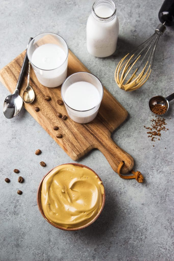 Two glasses of milk on top of a chopping board surrounded by a bottle of milk, a wire whisk, a couple of teaspoons, and a few coffee beans