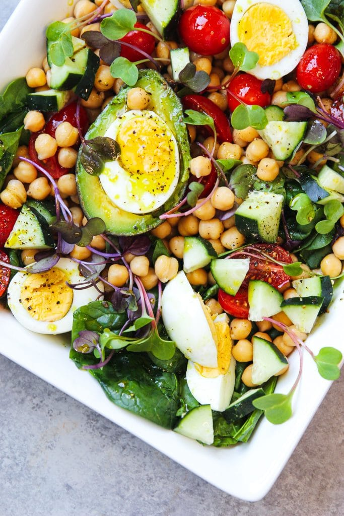 chickpea salad platter with fresh grape tomatoes, cucumber slices, avocado and hard boiled eggs