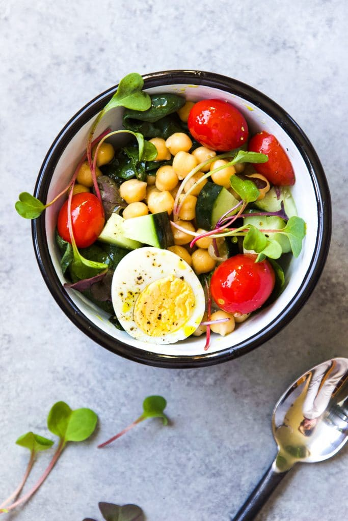 chickpea salad bowl with fresh grape tomatoes, cucumber slices, avocado and hard boiled eggs