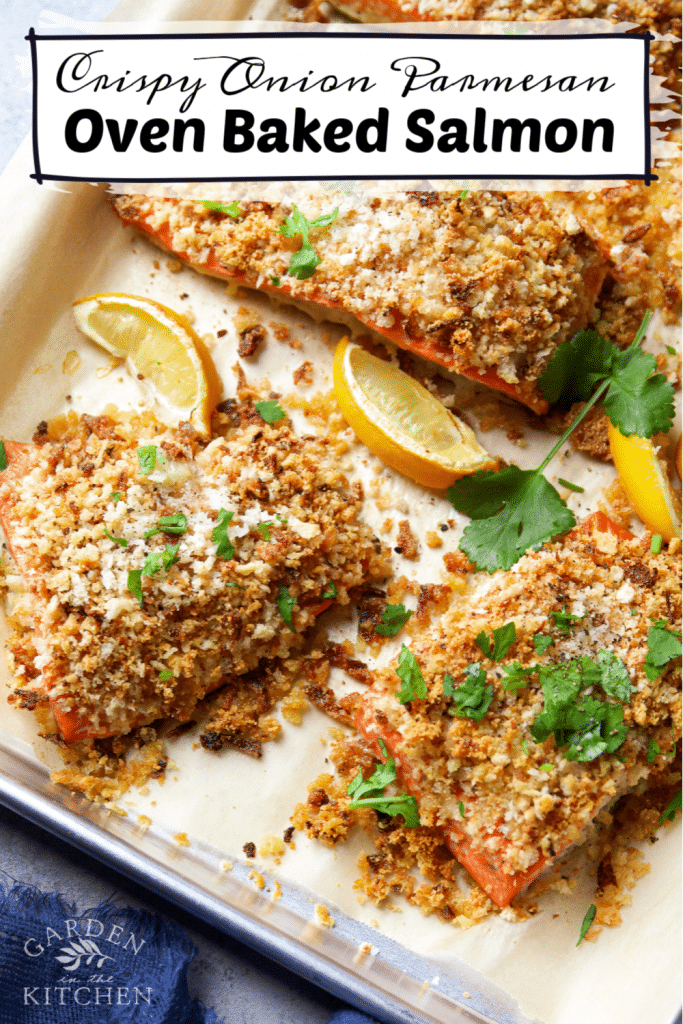 Onion Parmesan Crusted Salmon topped chopped parsley and surrounded by lemon slices on a tray lined with parchment paper