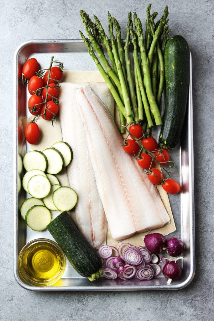 fish in foil recipe ingredients. tow large Black cod filets, fresh asparagus, zucchini, grape tomatoes, olive oil and red onions