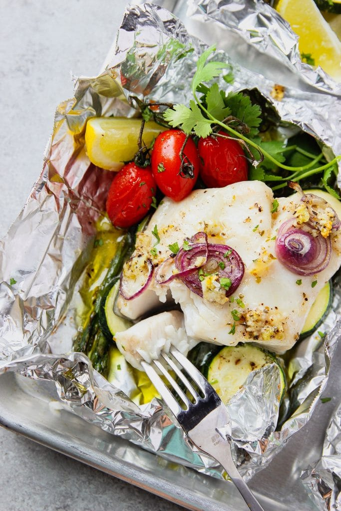 fish baked in foil with asparagus and zucchini, topped with red grape tomatoes and red onion slices. Garnished with fresh cilantro and lemon slice. Served on a sheet pan