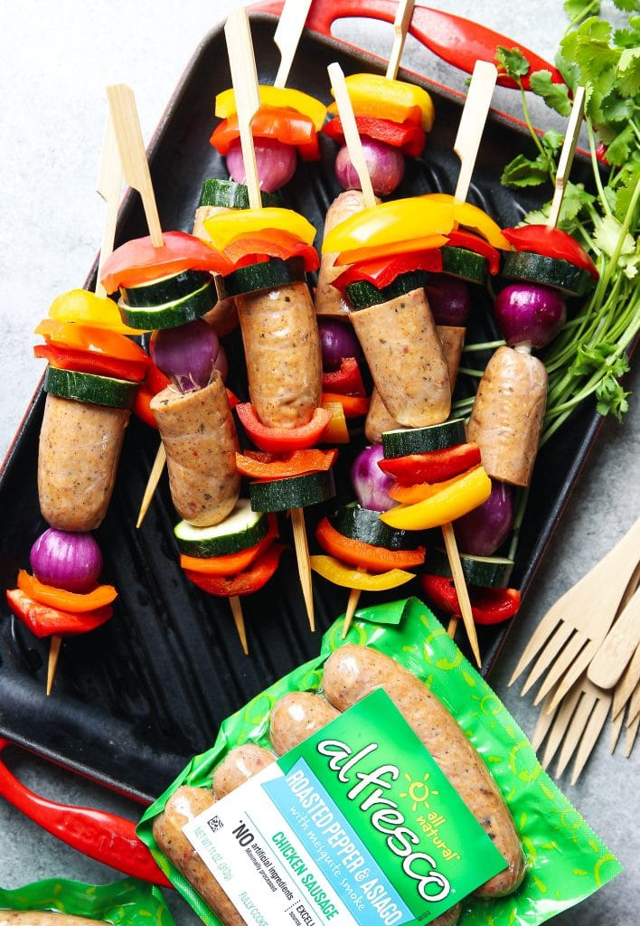 Lined up in a tray are cut up veggies and sausages sliced in half on serveral skewers.