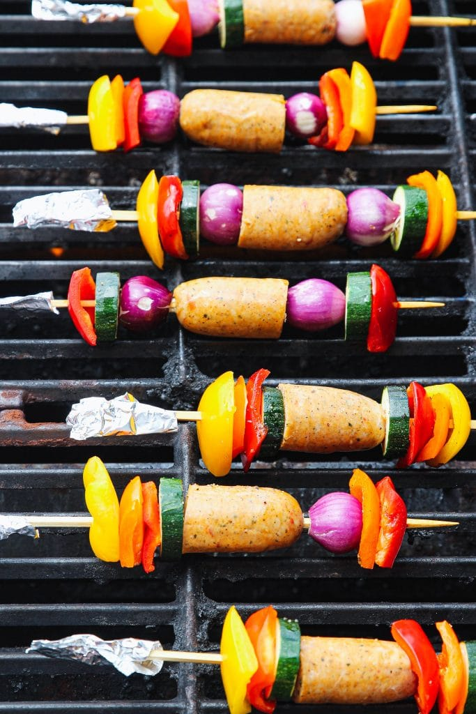 Sausage and veggie kabobs on the grill, a foil covers each end of a  wooden skewer.