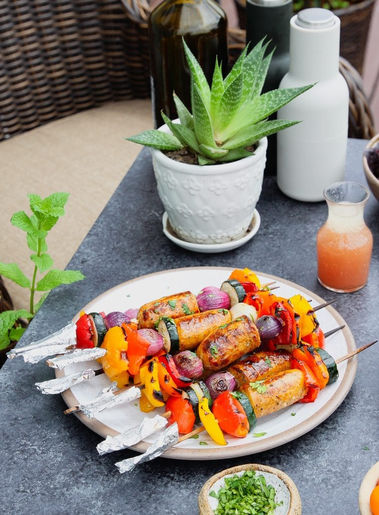 Chicken sausage and veggies kabobs served on a plate with a small glass container of dressing and a small bowl of chopped cilantro leaves.