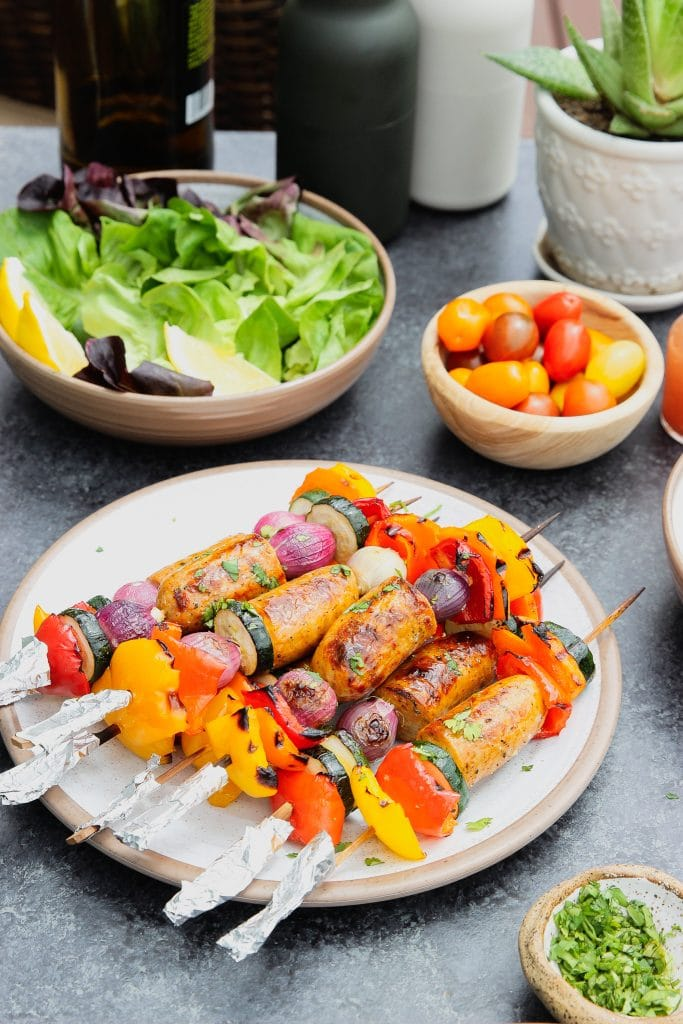 Veggies and sausage kabobs on a white plate surrounded by a bowl of salad greens and a bowl of cherry tomatoes