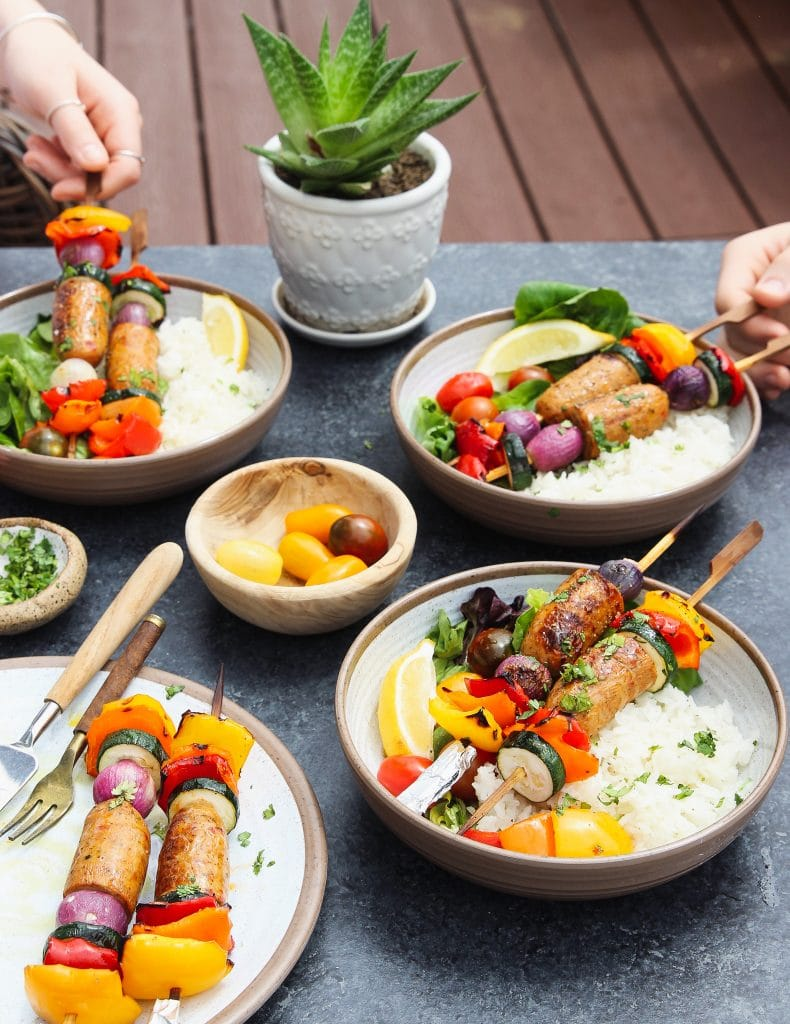 Sausage kabobs served on four plates with rice and green salad with a small pot of plant in the background.