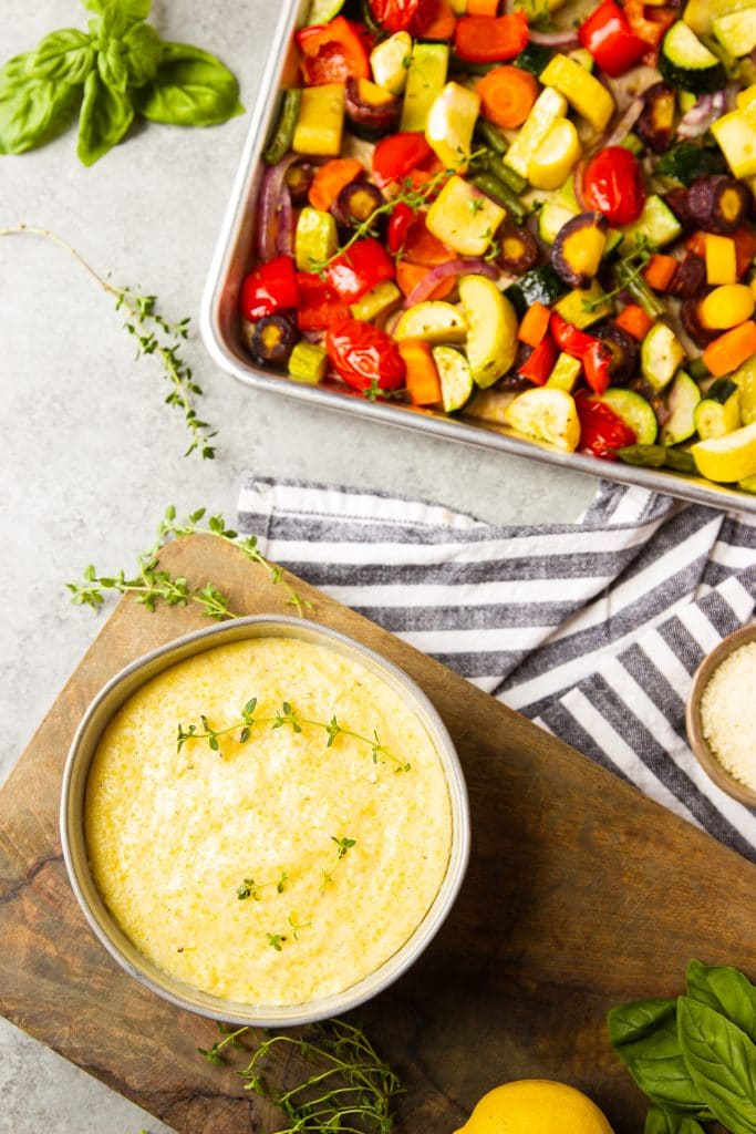 creamy polenta in a bowl sitting on a wooden board with fresh herbs. Roasted vegetables in a sheet pan