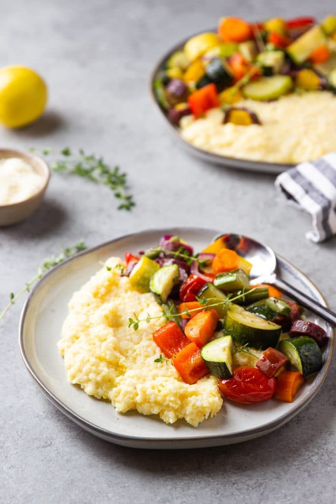 Roasted Vegetables zucchini, peppers, tomatoes over creamy polenta on a round plate with silver spoon