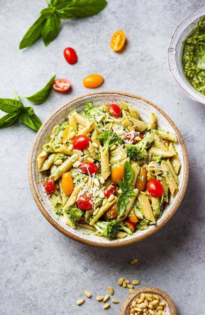 round bowl of pesto pasta with tomatoes, broccoli, pine nuts and fresh basil.