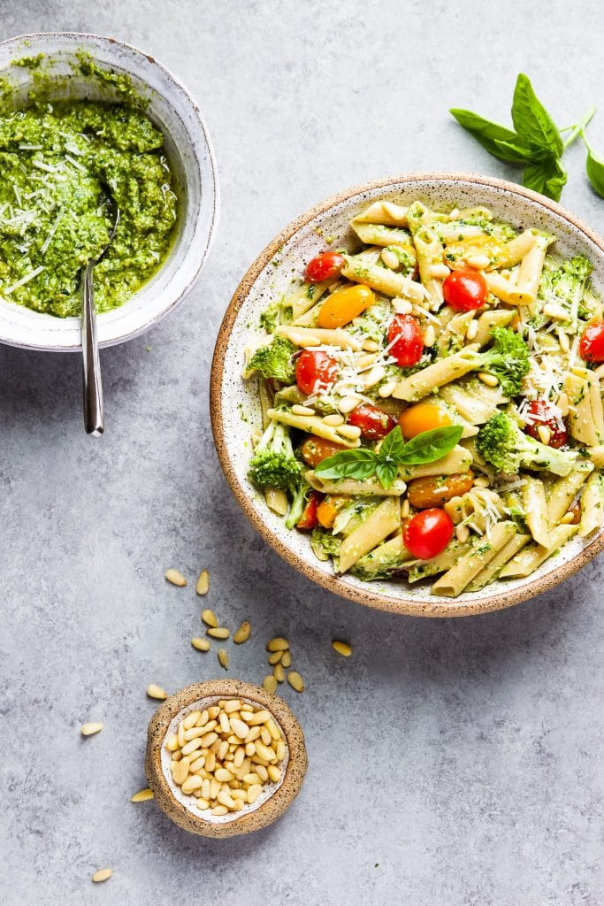Pesto pasta salad with fresh tomatoes, broccoli and pine nuts. Small white bowl with basil pesto and a silver spoon.