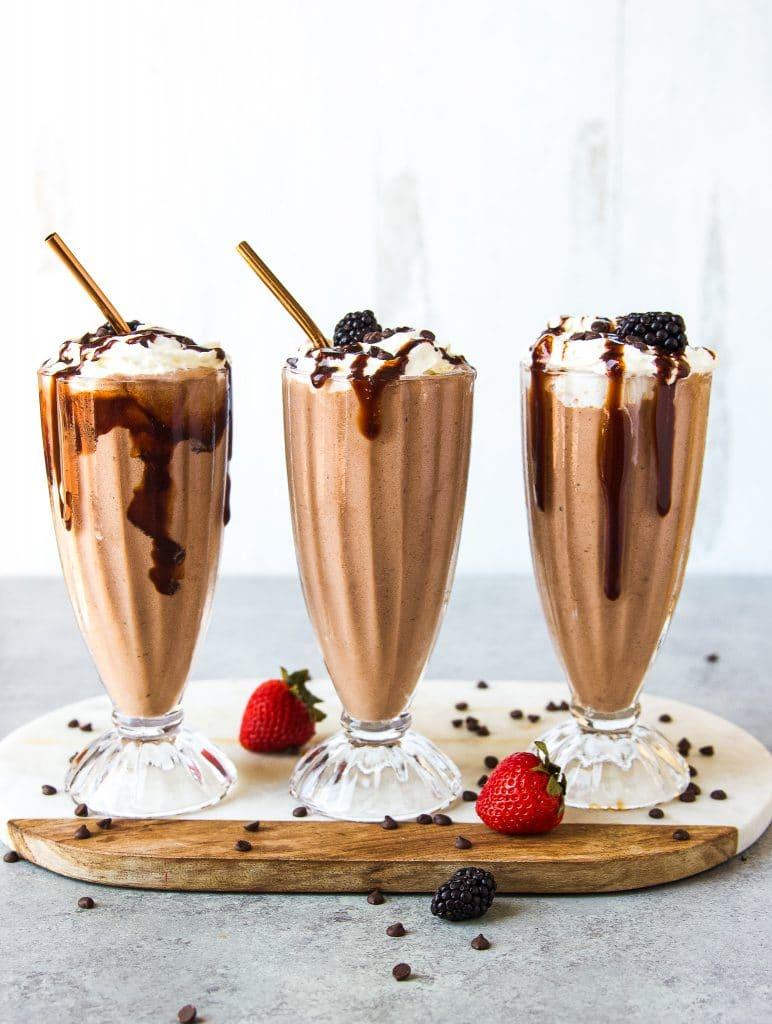 three milkshake glasses with chocolate banana milkshake, topped with whipped cream, chocolate syrup and blackberries.