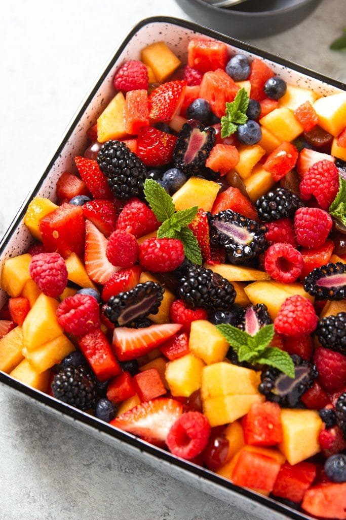 watermelon, berries, cantaloupe fruit salad in square dish with mint leaves.