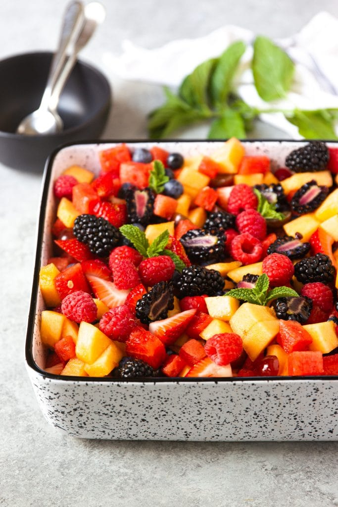 watermelon, berries, cantaloupe fruit salad in square dish with mint leaves. black round serving bowl with two spoons.