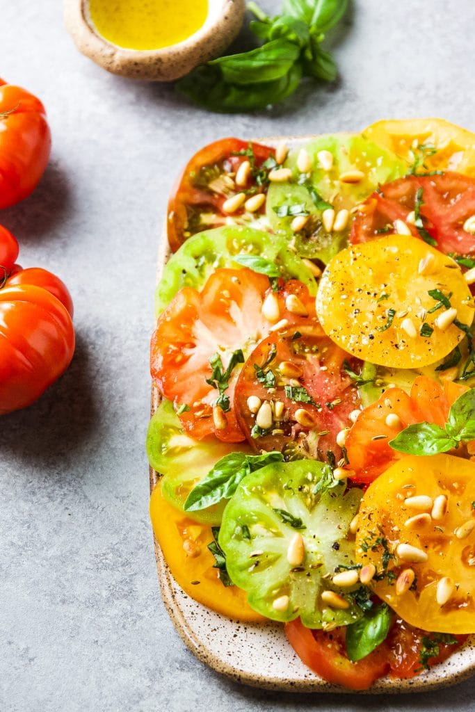 Green, yellow, orange and red slices of heirloom tomatoes on a rectangular platter. Garnished with pine nuts and basil